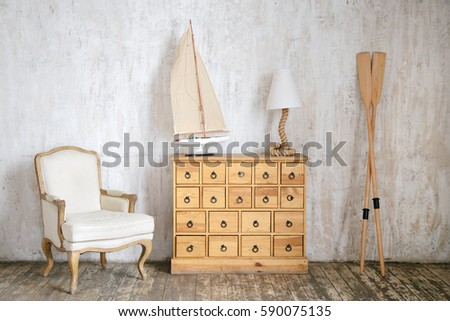 Modern interior photo of cabinet with drawers, rope shaped lamp, cloth armchair, sailing ship model and oars. Concrete wall and wooden floor background.