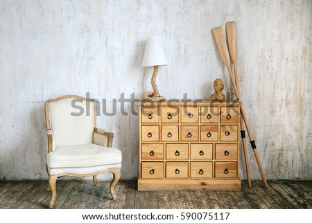 Shutterstock Modern interior photo of cabinet with drawers, rope shaped lamp, wooden abstract man bust model, cloth armchair and oars. Concrete wall background.