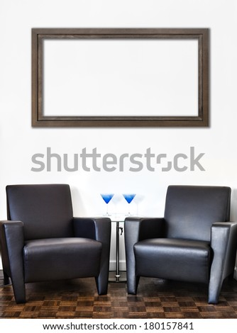 Modern Interior Room and white wall and big empty Painting Frame with space for your text. Two luxurious couch and glass table with accessories of your choice.