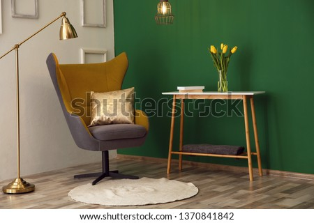 Modern interior with comfortable armchair and table near color wall #1370841842