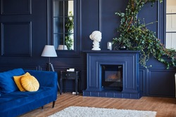 Modern interior with fireplace, spacious living room with dark blue walls and wooden floor. A real photo of the interior.