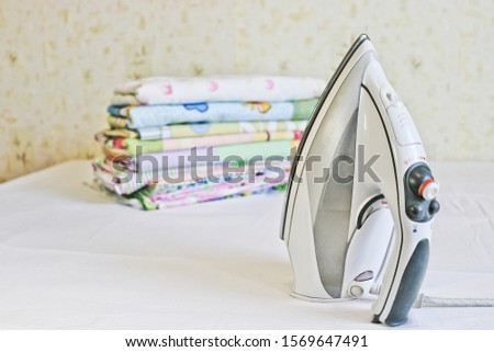 Modern iron and stack of ironed linen. Household chores. #1569647491