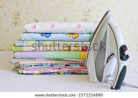 Modern iron and stack of ironed linen. Household chores. #1571256880