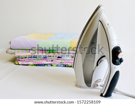 Modern iron and stack of ironed linen. Household chores. #1572258109