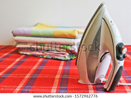 Modern iron and stack of ironed linen. Household chores. #1572962776