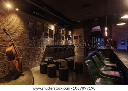 Modern jazz bar interior design, stage with cello, lamps above bar counter