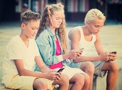 Modern kids spending time together outdoors using mobile gadgets