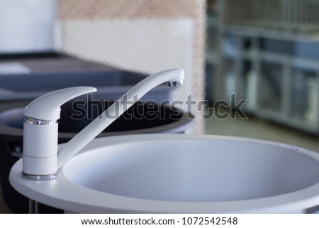 Modern kitchen and bathroom water faucets in the store #1072542548