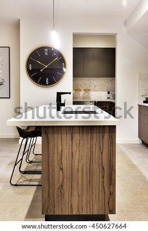 Modern kitchen countertop made in wood with a wall watch and chairs of a luxury house #450627664