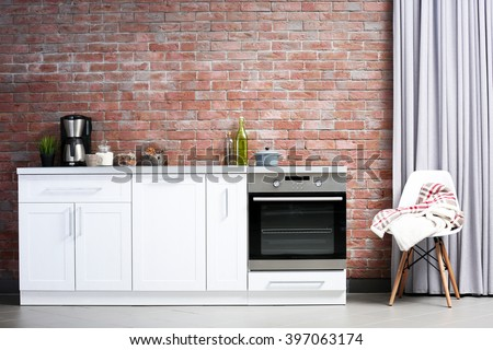 Modern kitchen furniture against brick wall background