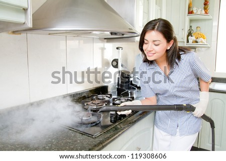 Modern kitchen - happy woman steam cleaning