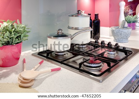 modern kitchen hob with pans and utensils