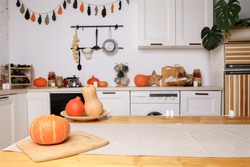 modern kitchen in light colors with autumn decor, orange pumpkins for Halloween, handmade garland on the wall, stylish furniture and dishes