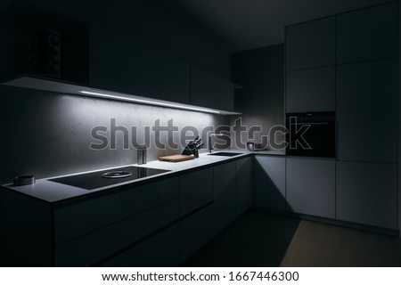 Modern kitchen in minimalist design during night with LED light strip, modern appliances and premium materials such as glass, concrete and wood. Kitchen is complemented by basic kitchen utensils.
