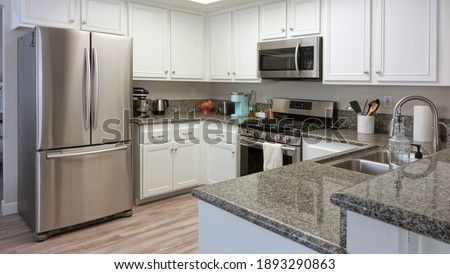 Modern kitchen interior with dark granite counters and stainless steel appliances, single family home in California