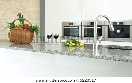 Modern kitchen interior with vegetables, glasses of wine and flowers