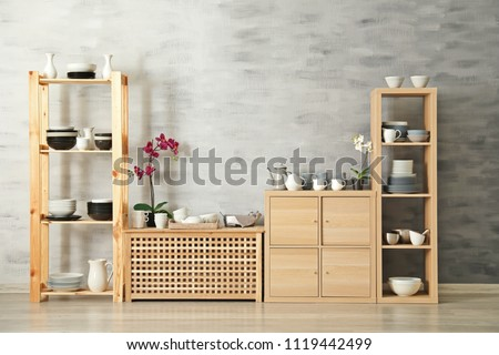 Modern kitchen interior with wooden storage stand and ceramic dishware on light wall background