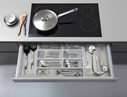 Modern kitchen, Open drawers, Set of cutlery trays in kitchen drawer. Plastic equipment for drawer inserts.