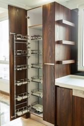 Modern kitchen, opened wooden drawers with accessories inside, solution for kitchen storage, minimalist interior design
