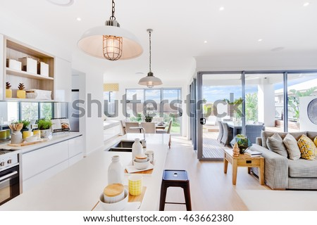 Modern kitchen with a dining and patio area including some utensils on counter top under the hanging lamps closely, the living room with sofa and pillows beside outdoor patio area with sunlight  #463662380