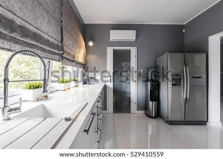 Modern kitchen with big windows, elegant kitchen units and silver fridge