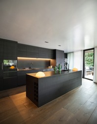 Modern kitchen with black furniture and wooden floor
