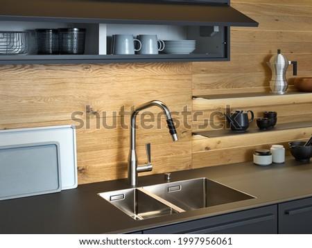 Modern kitchen with black furniture and wooden wall, black worktop have Stainless steel undermount kitchen sink and Tap water in the kitchen. dark tone kitchen