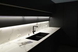 Modern kitchen with black furniture, White marble worktop and backsplash.Black sink and tap, Light under wall cabinet.
