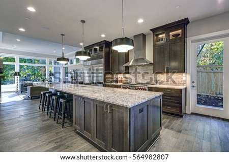 Modern kitchen with brown kitchen cabinets, oversized kitchen island with bar stools, granite countertops, huge refrigerator and beige backsplash. Northwest, USA  #564982807