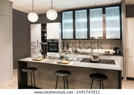 Modern kitchen with center island and bar stools with modern cabinetry and appliances in neutral shades of brown and beige #1445747015