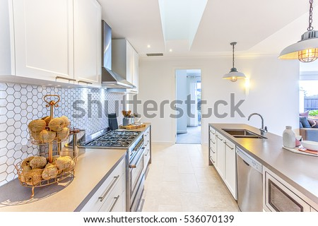 Modern kitchen with fancy items like thread balls on a small rack on the counter which has a stove next to the hallway to the door. There are hanging lamps flashing over the counter with sink and tap #536070139
