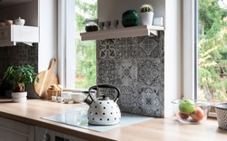 Modern kitchen with grey design tiles and wooden furniture. Big window and plant in scandinavian interior of kitchen. Cozy home in white color.