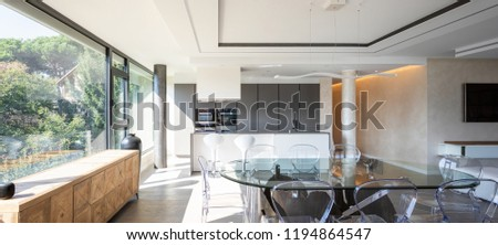 Modern kitchen with island and transparent chairs and table. Nobody inside #1194864547