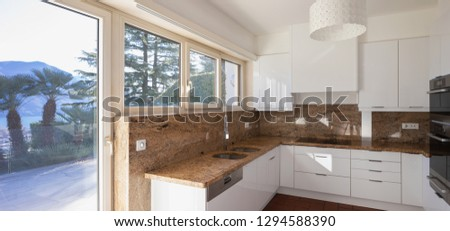 Modern kitchen with marble top and lake view. Nobody inside