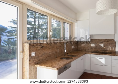 Modern kitchen with marble top and lake view. Nobody inside #1294588393