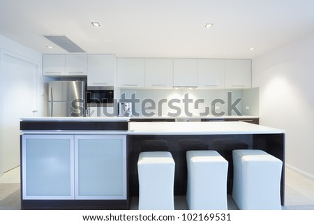 Modern kitchen with stainless steel appliances and white chairs