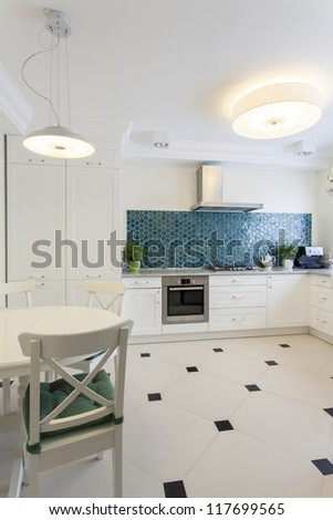 Modern kitchen with white furniture and tiles - stock photo