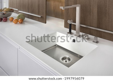 Modern kitchen with white furniture and white worktop have  undermount kitchen sink and Tap water in the kitchen. white tone  and clean kitchen.