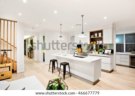 Modern kitchen with white walls illuminated by hanging lamps  at night beside the wooden hallway through the luxury house and stairs