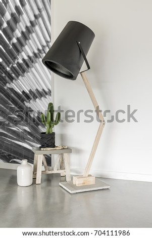 Modern lamp in a minimalist room with a cactus on a stool #704111986
