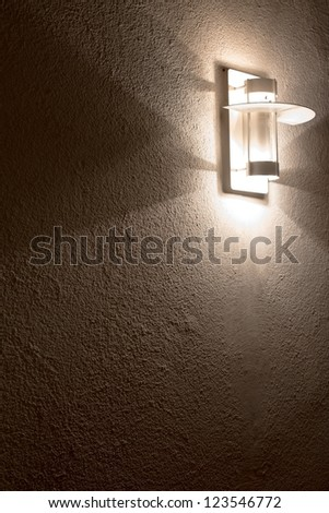 Modern lamp on concrete wall with great shadows