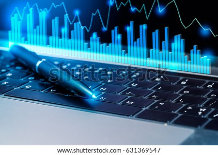 Modern laptop computer and business investment graphs