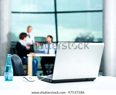 Modern laptop on foreground at empty workplace. Team of young businesspeople discussing plans on background