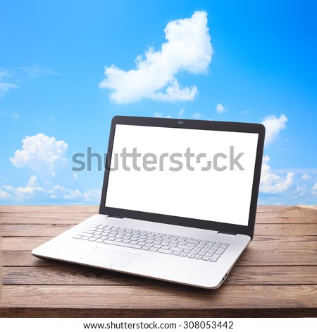 Modern laptop with a white screen on wooden table workplace. Mock up for design. Top view