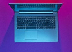 Modern laptop with vibrant gradient pink blue neon  lights. Minimalism. Top view
