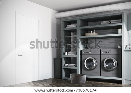 Modern laundry room interior with white and brick walls, gray wooden consoles and shelves and two gray washing machines. Side view. 3d rendering mock up #730570174