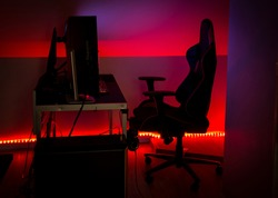 Modern LED red ambient light around gaming computer set at home. Home decor concept.