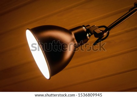 Modern LED wall lamp with a burning lamp.