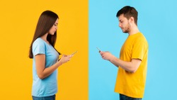 Modern Lifestyle And Communication Concept. Side view portrait of man and woman chatting on cell phone, isolated over blue and yellow studio background. Serious couple texting sms in social media