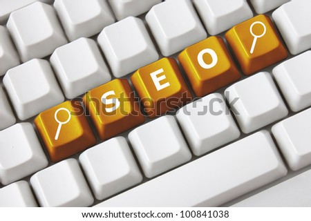 Modern light computer keyboard with a SEO text and magnifying glass symbol on buttons. Search engine optimization concept